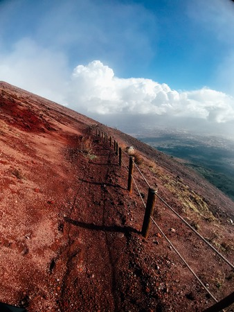 A mountain path bordered by red cliffs Banco de Imagens