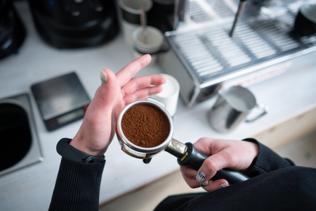 Barista holding portafilter with ground coffee Stockfoto - 110078126