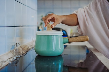Pot and vegetables in modern kitchen Stock Photo