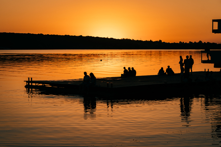 People rest on the river bank. Sunset