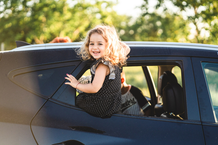 A little girl is sitting on the door of the car