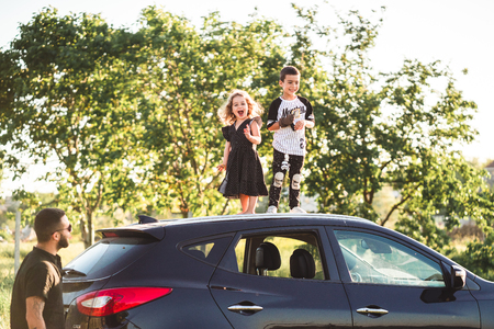 Two children stand on the roof of a car 스톡 콘텐츠
