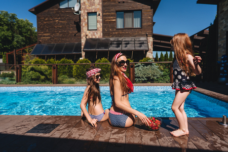 Happy mother and two daughters in swimsuits at border of pool.