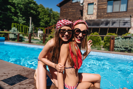 Mother and daughter in swimsuits at border of pool.