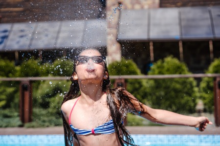 Girl sprinkles water from her mouth, outdoor