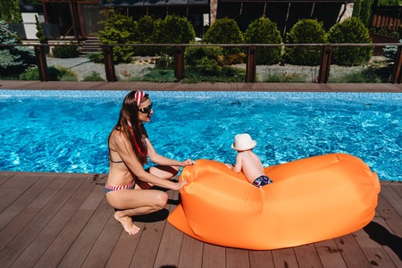 Beauty mother with littel son by the pool