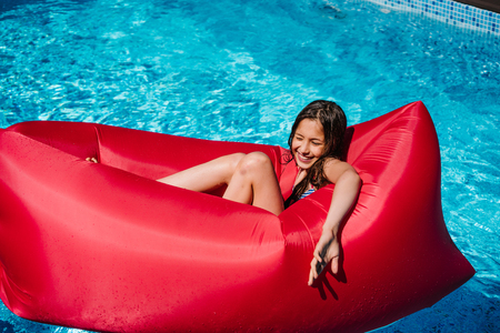 teen girl on a red chaise longue