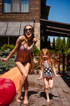Mom and daughter near the pool, outdoor Фото со стока