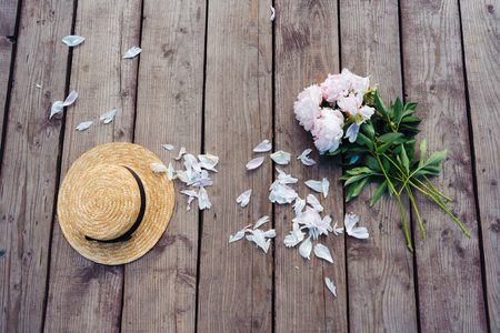 On a wooden pier lies a womans hat and a bouquet of peonies. Banco de Imagens