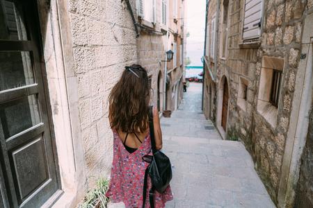 A young girl walks along a narrow Italian street Archivio Fotografico - 109401314