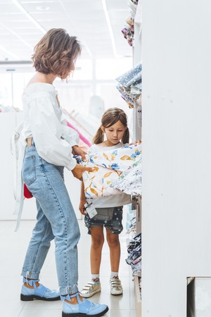 Mom and daughter in the fabric store choose fabric Stock Photo