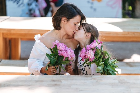 Mother and daughter kissing bouquets of peonies