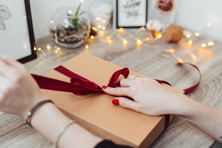 Woman wrapping present in paper with red ribbon. Stock Photo