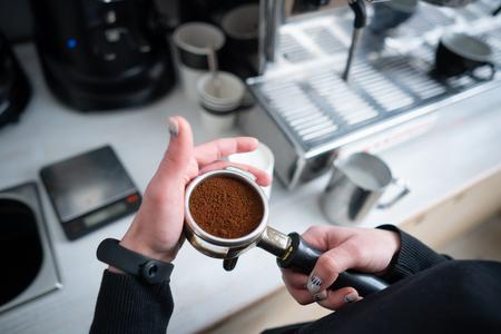 Barista holding portafilter with ground coffee Stockfoto - 109901692