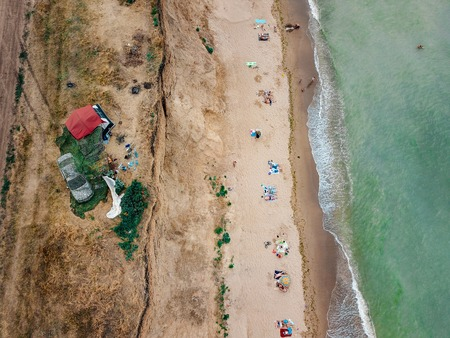 People rest on the wild beach with their families. Aerial photography Foto de archivo - 110912579