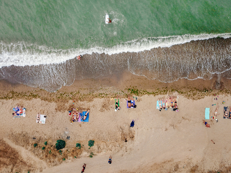People rest on the wild beach with their families. Aerial photography Foto de archivo - 110912664