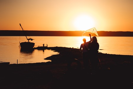 A young couple on the shore launches a kite, against the sunset