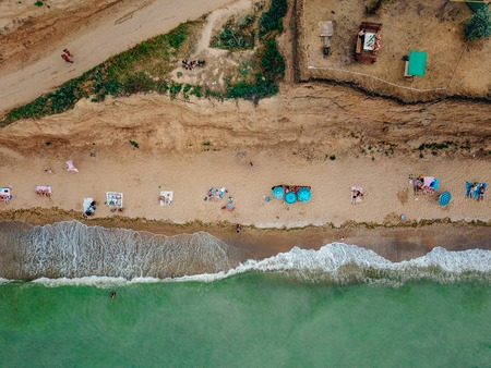 People rest on the wild beach with their families. Foto de archivo - 110913816
