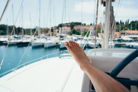 Female foot in the background of a moored yacht Stock Photo