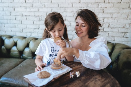 girl with her mother eats oatmeal cookies and have fun Stock Photo