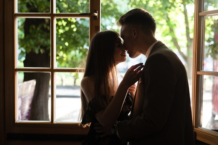 Young couple in love standing by the window