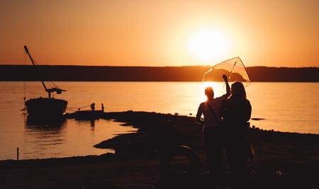 A young couple on the shore launches a kite Archivio Fotografico