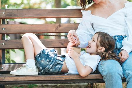 Mom feeds her little daughter ice cream in the park Reklamní fotografie - 113097059