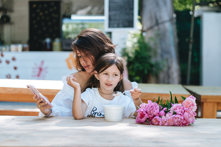 Young mother and little daughter together in a cafe.