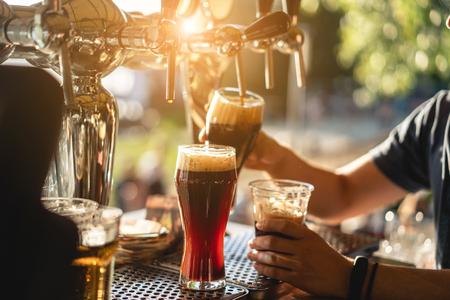 bartender pours a dark beer close up Imagens
