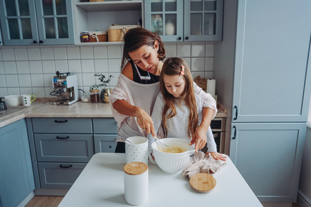 mom teaches her little daughter to cook food Фото со стока