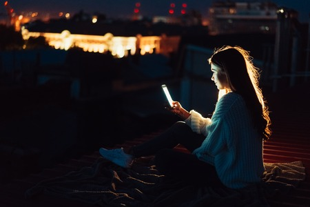Young girl sits at night on the roof of a house. Beautiful evening