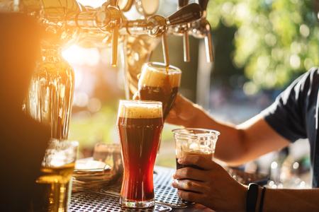 Camarero vierte una cerveza oscura de cerca Foto de archivo