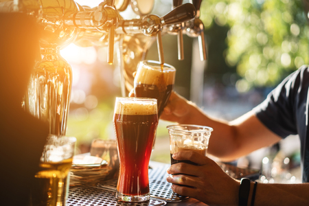 il barista versa una birra scura da vicino Archivio Fotografico