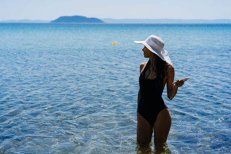 Young girl in a bathing suit and a striped hat is standing in the blue sea