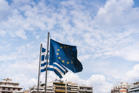 Flags of Greece and the European Union are developing on flagpoles. Imagens
