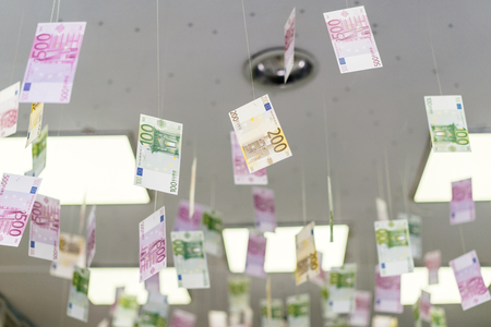 Cash bills hang on the thread from the ceiling.