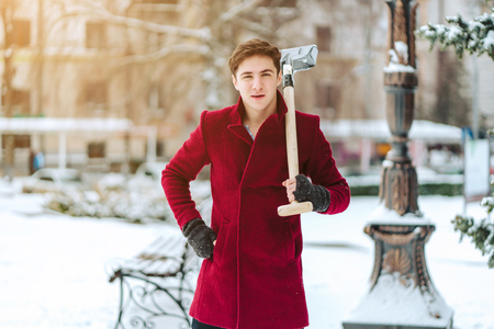 Young man holding shovel outdoors