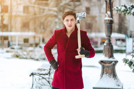 Young man holding shovel outdoors Foto de archivo - 113299945