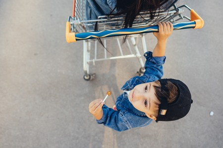 Little boy is driving his mother in a cart. Stok Fotoğraf