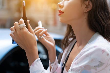 Hermosa mujer sosteniendo lipstic rojo y haciendo maquillaje rápido Foto de archivo
