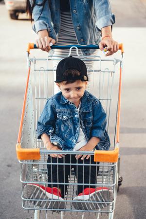 Small boy, Mom carries in a cart near the supermarket. Foto de archivo - 113837175