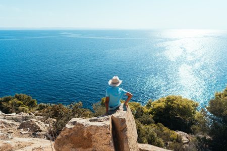 boy sitting on a rock with seascape on the background