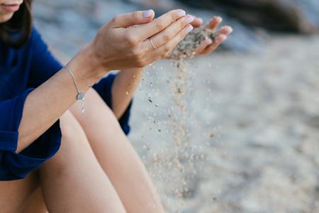Detail of sand running through open hands. Stock Photo
