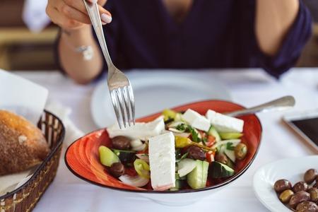 Greek salad, female hands hold a fork. Stock Photo