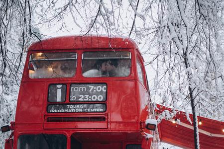 Liebevolle junge Paare, die sich im roten Bus küssen, genießen Sie einander