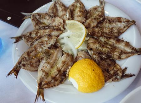 Small fried fish appetizer served with lemon Standard-Bild - 114033367