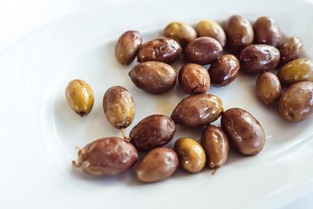 On the plate lie large, pickled Greek olives.