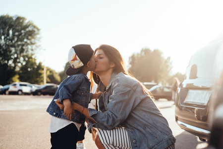 A boy kisses his beloved mother in the parking