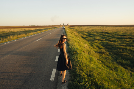 A young girl is walking along the road. She looks around. Stock Photo