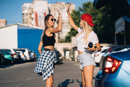 Two young girls in sunglasses posing for the camera on the car parking. Reklamní fotografie